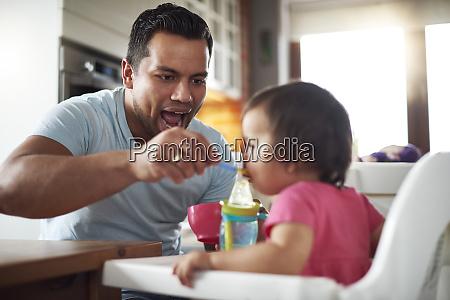 father feeding baby girl sitting in