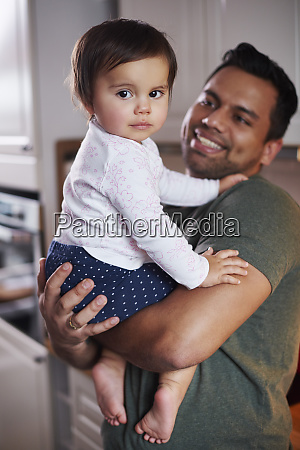 portrait of smiling father holding baby