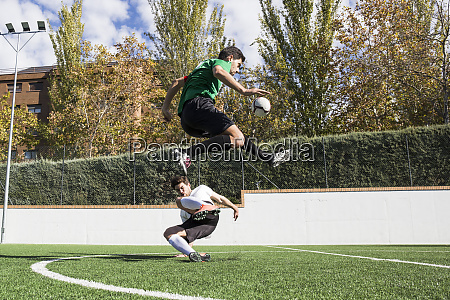 determined football player kicking ball on