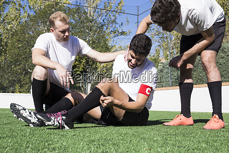 football players helping an injured player