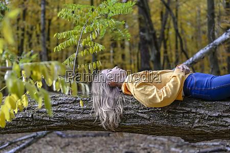 girl lying on tree trunk in