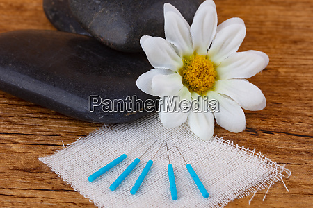 spa stones with acupuncture needles