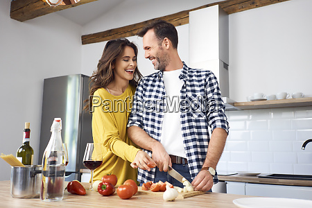 affectionate couple in kitchen preparing spaghetti