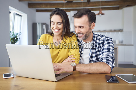 couple sitting at dining table using