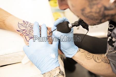 tattoo artist tattoing hand