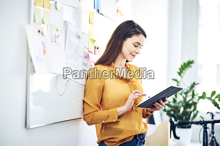 smiling businesswoman using tablet at whiteboard