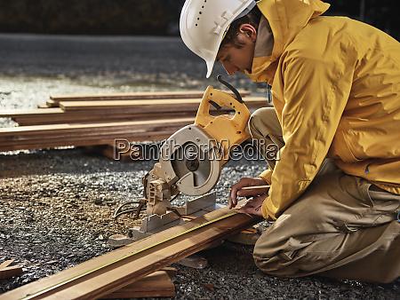 man measuring decking board circular saw
