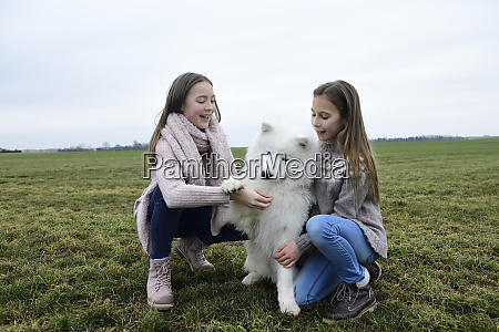 two girls crouching on a meadow
