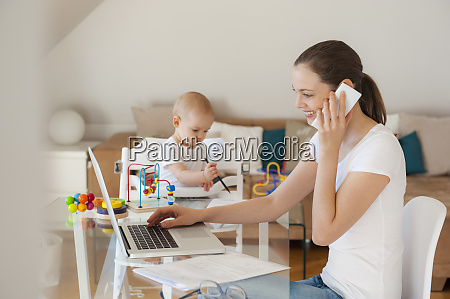 smiling mother using laptop and cell
