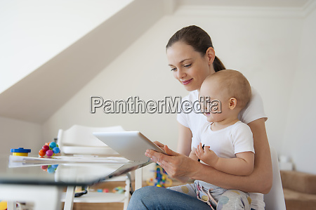 mother and little daughter using tablet
