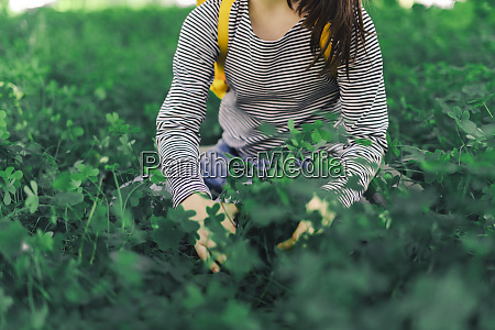 girl picking clover partial view
