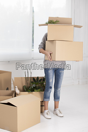 unrecognizable woman carrying cardboard boxes in