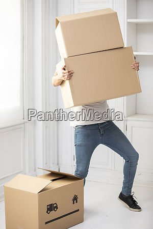 unrecognizable man carrying cardboard boxes in
