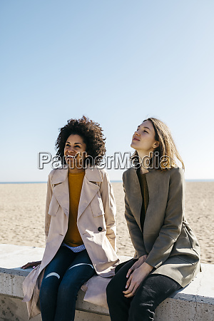 two friends sitting on the promenade