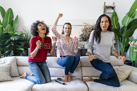 three excited women on couch at