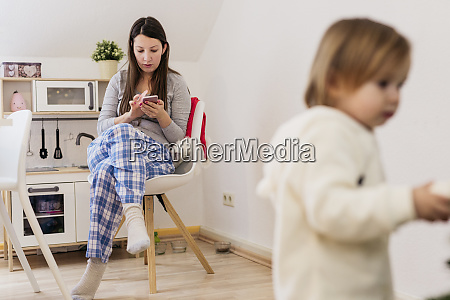 woman sitting in kitchen using smartphone