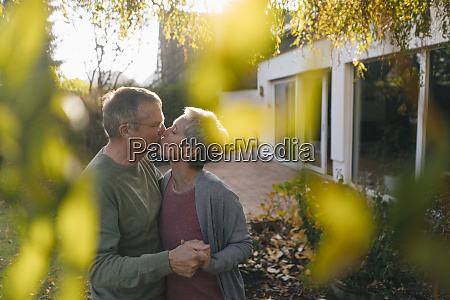 affectionate senior couple kissing in garden