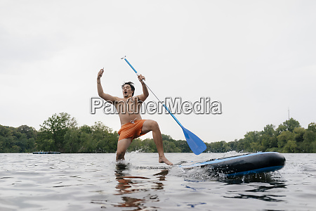 man falling from sup board while