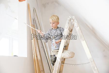 boy with pocket rule on ladder