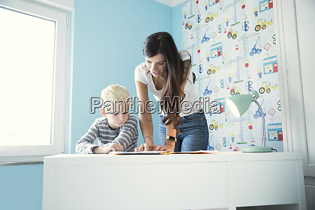 mother helping son doing homework at