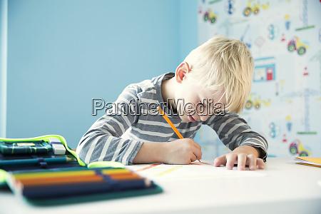 focused boy doing homework at desk