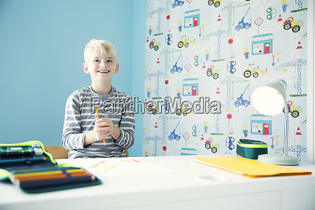 smiling boy doing homework at desk