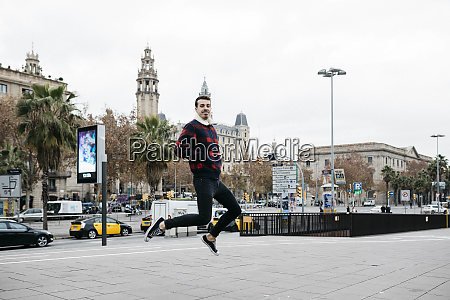 young man wearing casual clothes jumping