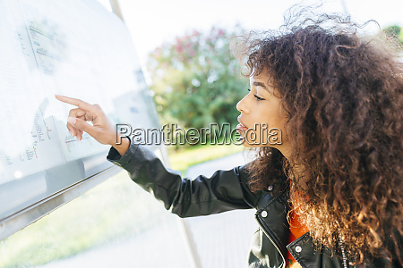 young woman looking at schedule at