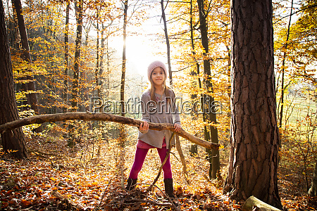 young girl holding branch in autumn