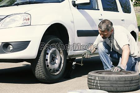 mature man changing car tires top