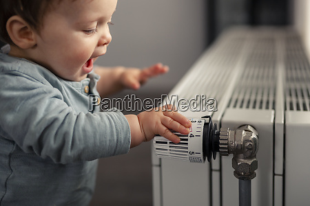 excited baby boy playing with thermostat