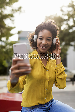 portrait of smiling woman listening music