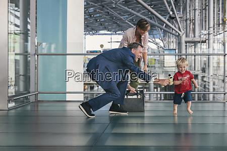 happy child running around travelling businessman