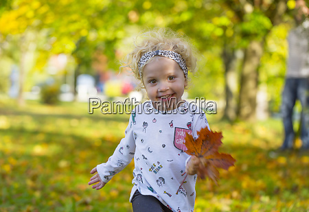 happy little girl running with autumnal