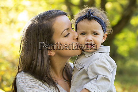 mother kissing baby girl outdoors in