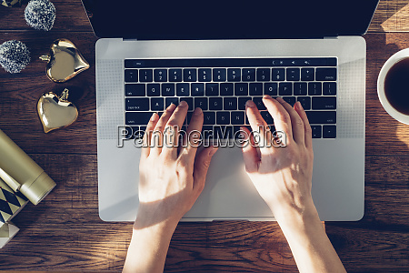 womans hands typing on laptop top