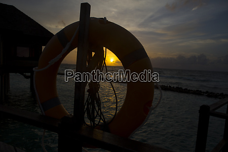 maldives lifebelt and sunset above the