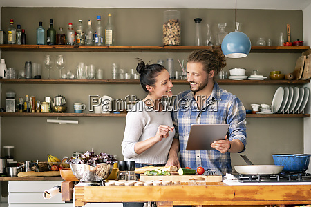 young couple preparing spaghetti together using