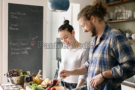 young couple preparing food together tasting