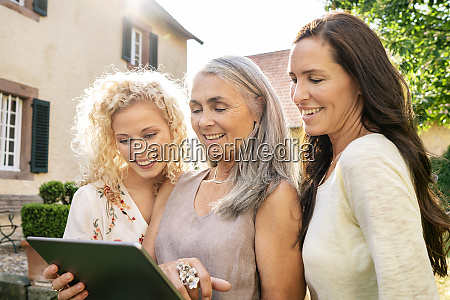 three smiling women of different age