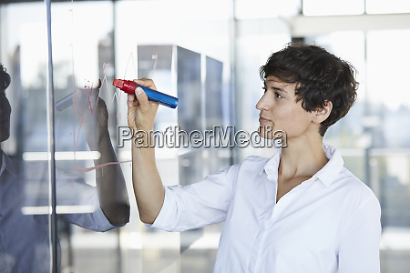 businesswoman drawing chart on glass pane