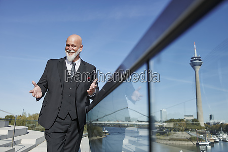 elegant businessman standing on a bridge