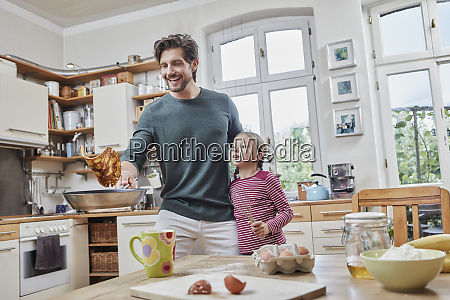 happy father and daughter baking pancakes