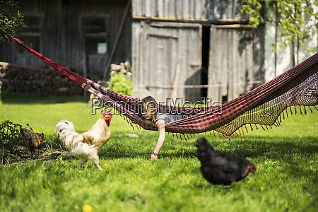 girl relaxing in hammock in garden