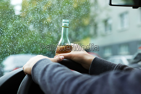 drunk young driver drinking a bottle