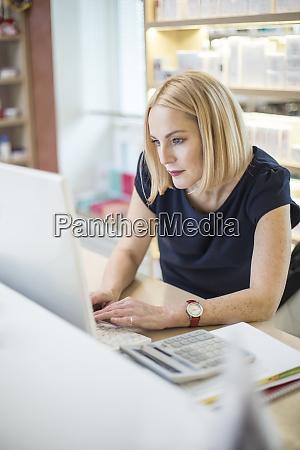 female hairdresser typing on tastature