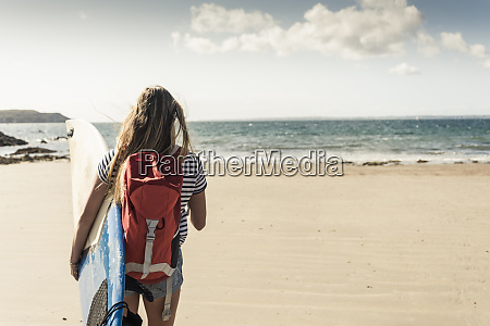 young woman with backpack walking on