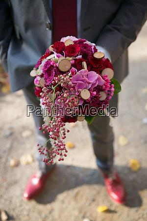 elegant man holding bunch of flowers