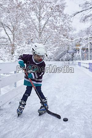 boy playing ice hockey on the
