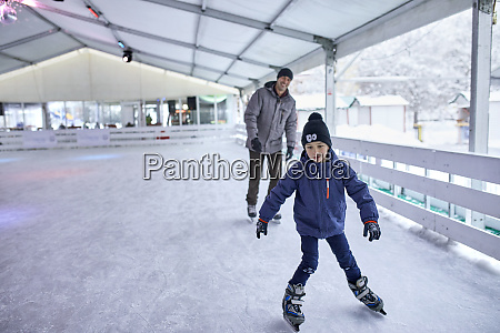 father and son ice skatng together